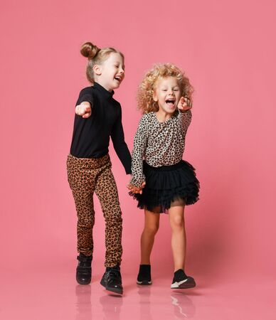 Two cheerful screaming kids girls friends sisters in leopard print clothes pants and shirt runs towards us pointing fingers at us over pink background