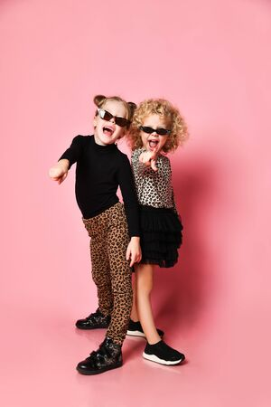 Two cheerful screaming kids girls friends sisters in leopard print clothes pants and shirt stand back to back pointing fingers at us over pink background Stok Fotoğraf