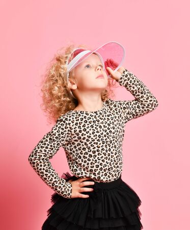 Portrait of stylish blonde curly kid girl in leopard print sweatshirt and black skirt looks up in the sky holding fashion visor cap over pink background
