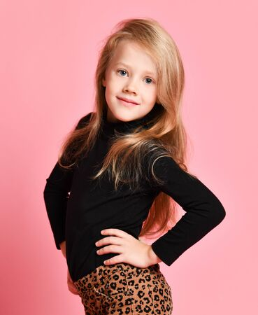 Portrait of cute blonde kid girl in black sweatshirt and leopard print pants posing sideways to us with her hands on her hips over pink background