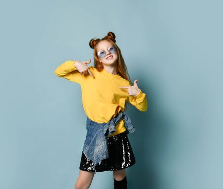 Happy smiling red-haired teenager girl in stylish glasses, glossy black skirt and denim jacket is pointing fingers of both hands at free copy space on her yellow sweatshirt