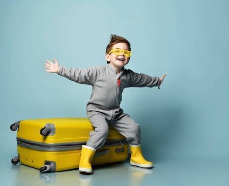 Little brunet child in gray overall, yellow sunglasses and rubber boots. Sitting on suitcase, smiling, spread hands, posing on blue background. Childhood, fashion, travelling. Full length, copy space