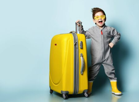 Little brunet model in gray overall, yellow sunglasses and rubber boots. He opened mouth, holding suitcase, posing on blue studio background. Childhood, fashion, travelling. Full length, copy space