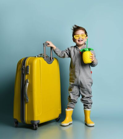Little kid in gray overall, yellow sunglasses, rubber boots. Smiling, holding suitcase and cocktail bottle in form of pineapple, posing on blue background. Travelling concept. Full length, copy space