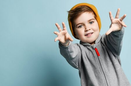 Little brunet male in orange hat and gray overall. He is smiling, reaching his hands to you, posing against blue studio background. Childhood, fashion, advertising. Close up, copy space