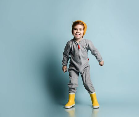 Little brunet model in orange hat, gray overall and yellow rubber boots. He is smiling while posing against blue studio background. Childhood, fashion, advertising. Full length, copy space