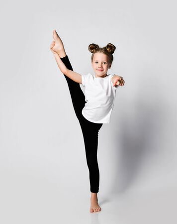 Athletic blonde kid girl does gymnastic exercises at home in studio vertical splits holding leg with one hand and pointing finger at us with the other on white background 写真素材