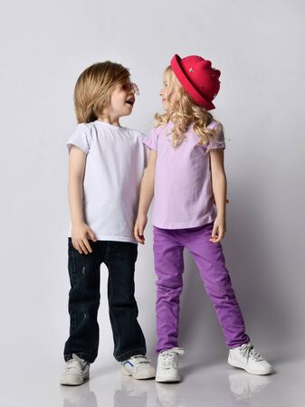 Little positive blond baby girl and boy sister and brother in stylish casual clothing and accessories standing and looking at each other over grey wall background. Happy childhood concept