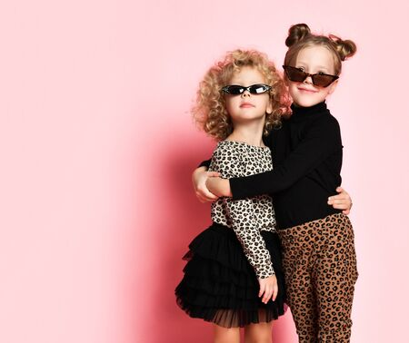 Two kids girls friends sisters in stylish sunglasses, leopard print clothes pants and shirt pose hugging over pink background with free text copy space