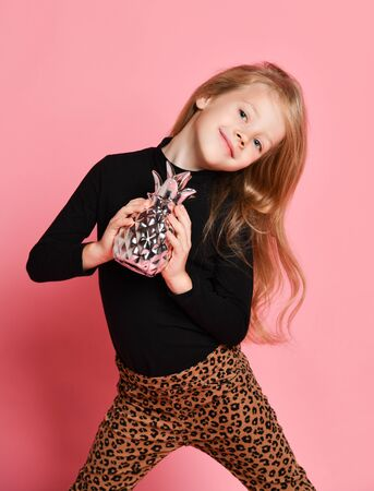 Nice smiling blonde kid girl in black sweatshirt and leopard print trousers poses with silver pineapple she holds in her hands over pink background