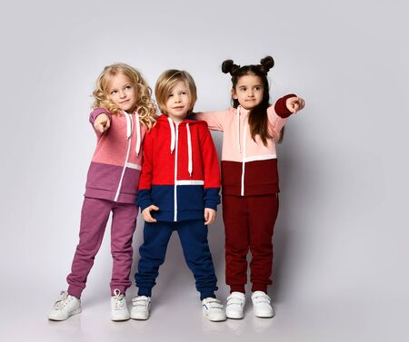 Full growth portrait of three kids blonde and brunette girls and blond boy in modern hoodies and pants stand together pointing fingers at us