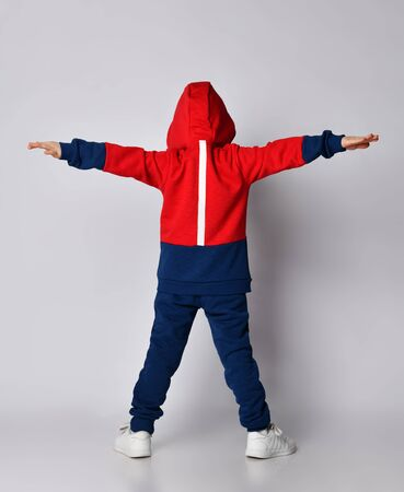 Full growth portrait of frolic laughing blond kid boy in red and blue sport suit standing back to us with hood on head and arms outstretched like wings over background