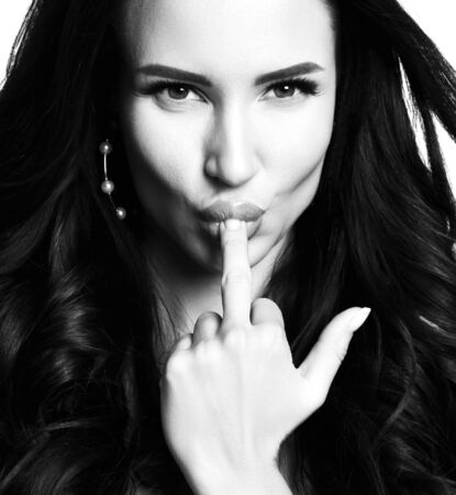 Portrait of young beautiful brunette woman with long hair in stylish earings licking middle finger over white background. Woman beauty and sex concept