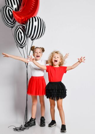Two happy singing blonde kids girls in red and black skirts and white and red t-shirts with big stylish air balloons stand together holding hands wide apart arms outstretched Stock Photo