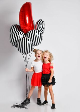 Two happy singing screaming blonde kids girls in red and black skirts and white and red t-shirts with big stylish air balloons stand together hugging Stock Photo