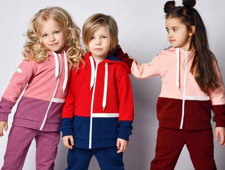 Three kids friends in modern sportswear are posing. Blonde girl is hugging blonde boy in sunglasses while brunette kid girl is standing near them