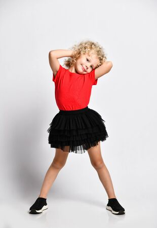 Playful frolic kid girl in black skirt, red t-shirt and sneakers stands with her legs wide apart and her hands behind her head at nape over white background
