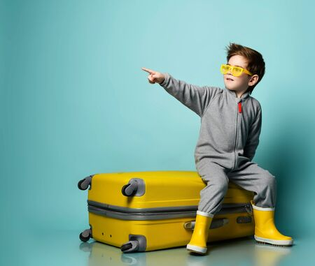 Little brunette kid in gray overall, yellow sunglasses and rubber boots. He sitting on suitcase, pointing at something, posing on blue background. Childhood, fashion, travelling. Full length, copy space