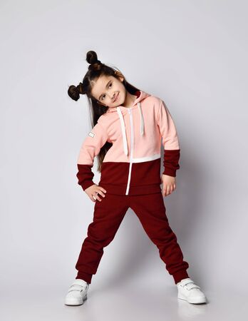 Frolic sly smiling kid girl with straight brunette hair with buns in two-colored pink brown sportswear hoodie and pants is standing with her head bowed aside looking