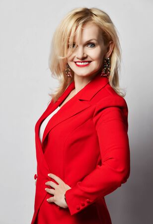 Portrait of young beautiful blond smiling woman happy smiling in stylish elegant deep red official suit and massive earrings over light wall background. Stylish office look concept