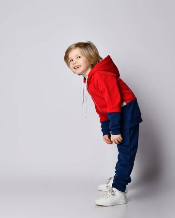 Full growth portrait of active blond kid boy in blue and red sportswear hoodie and pants doing exercises bending over reaching his hands to his toes