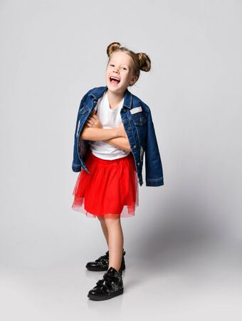Full growth portrait of frolic laughing blonde kid girl with funny buns hairstyle in red skirt, white t-shirt and denim jacket over shoulders