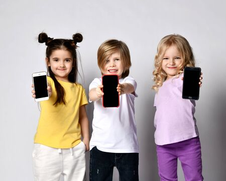 Portrait of three smiling children kids in casual clothes showing demonstrating us three blank switched off black screens of their modern smartphones Stockfoto