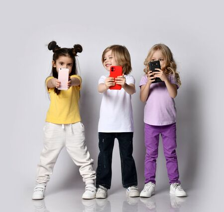 Three happy smiling kids boy and girls in t-shirts and pants are making selfie taking pictures video with their modern smartphones over white background Stockfoto