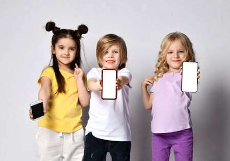 Portrait of three smiling children kids in casual clothes showing demonstrating us three blank screens of their modern smartphones Stockfoto