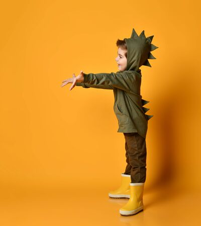 Cheerful kid boy in dark green hoodie with dinosaurs spikes at his back
