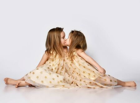 Two small beautiful girls sisters in same dresses with stars barefoot sitting on floor and kissing each other over grey