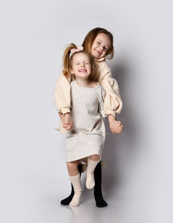 Two small beautiful smiling girls sisters in pastel colored home cozy clothing have fun together posing holding hands. Happy childhood, stylish home children clothes concept 版權商用圖片