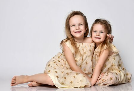 Two small beautiful smiling girls sisters in same dresses with stars sitting on floor and cuddling over grey background. Happy childhood, stylish home children clothes concept