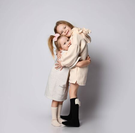 Two small beautiful smiling girls sisters in pastel colored home cozy clothing standing and hugging each other over grey background. Happy childhood, stylish home children clothes concept 版權商用圖片
