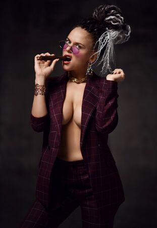 Young beautiful woman with dreadlocks hairstyle in sexy checkered suit with naked breast standing and biting cigar over dark background. Daring images for business style concept