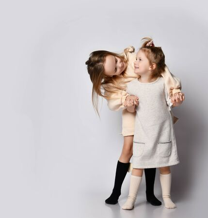Two happy smiling girls sisters in pastel beige cozy clothing stand behind each other over background with copy space. Happy childhood and stylish home children clothes concept 版權商用圖片