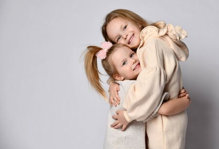 Portrait of two smiling girls sisters in pastel beige home cozy clothing hugging each other over background with copy space. Happy childhood, stylish home children clothes concept