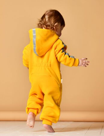Infant child baby boy kid toddler in yellow costume body overalls hoodie make first steps walking on beige background