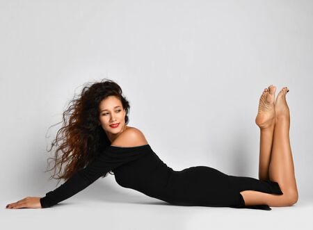 Woman with long curly brunette hair in black tight off-shoulder dress lies posing on the floor with her feet up and looks back over background with copy space above