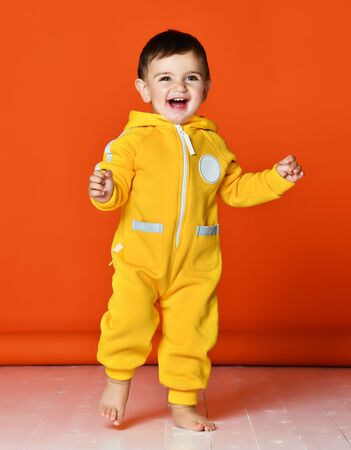 Infant child baby boy kid toddler in yellow costume body overalls hoodie make first steps walking on orange laughing background