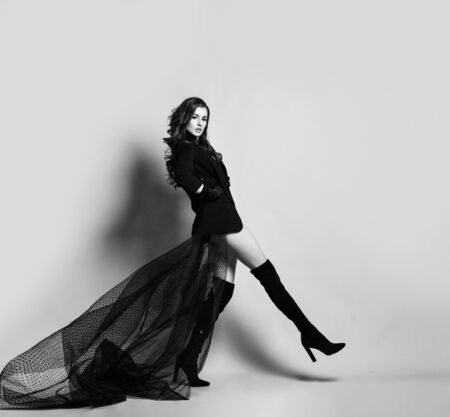 Young beautiful brunette woman in black clothes with long transparent hem and high boots making step and looking at camera over white wall background. Sexy feminine style concept
