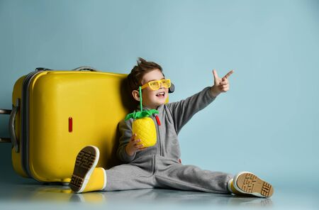 Happy kid boy in gray overall, yellow sunglasses, rubber boots sit on floor near roller bag, holding cocktail bottle in form of pineapple, pointing at free copy space upper corner