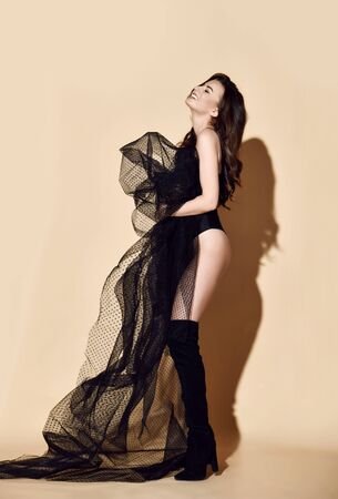 Young beautiful brunette woman in black swimsuit or underwear and high boots standing, holding black transparent cloth in hands and smiling over yellow wall background. Beauty of womans body concept Standard-Bild