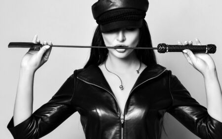 Portrait of brunette model in brutal black leather dress with zipper and leather cap holding a whip at mouth, touching it by her lips. Beauty, fashion,
