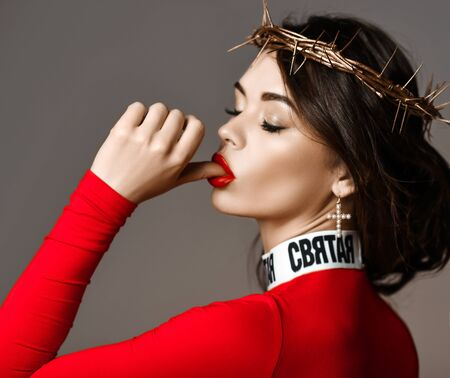 Portrait of seductive woman with a golden crown of thorns on her head in stylish red turtleneck sweater sucking kissing her finger thumb. Beauty, fashion, style, footwear concept