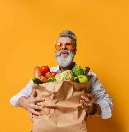 Happy adult grey haired stylish man with beard holding paper bag full of healthy food vegetables and fruits over yellow background. Clean eating and vegan food concept