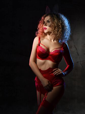 Gorgeous blonde curly woman in red lace lingerie, garter belt, stockings and veil is posing sideways against dark studio background with red backlight. Beauty, fashion.