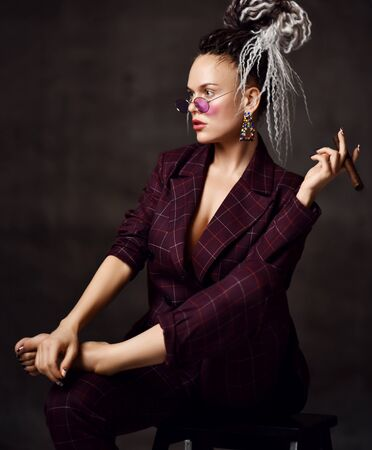 Young beautiful woman with dreadlocks hairstyle in sexy checkered suit sitting barefoot on chair and smoking cigar over dark background. Daring images for business style concept