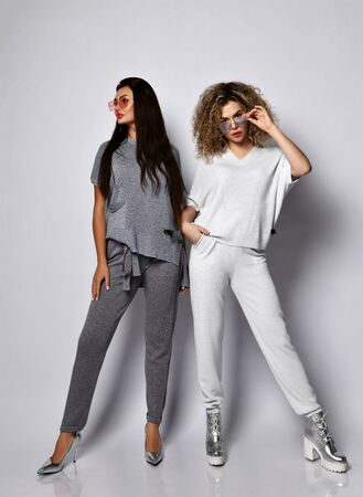 Two young beautiful women in comfortable cotton costumes and stylish footwear standing over grey wall background. Beauty, fashion, trendy outfit concept