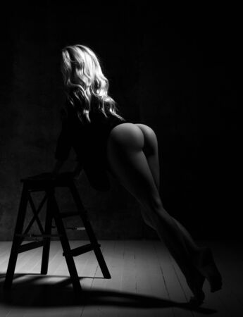 Beautiful sexy fitness woman standing and holding on ladder and showing perfect naked buttocks over dark background, rear view, black and white. Slim sexy body and booty concept Archivio Fotografico